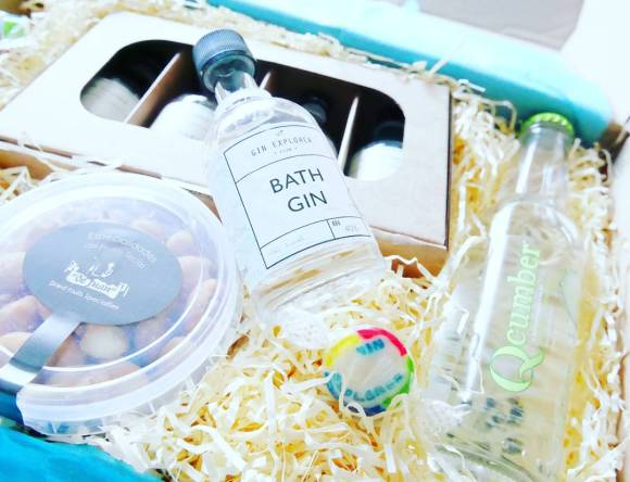 A box with another box containing gin samples, the Bath gin bottle the main focus of the picture and a bottle of cucumber infused water to the right of it.