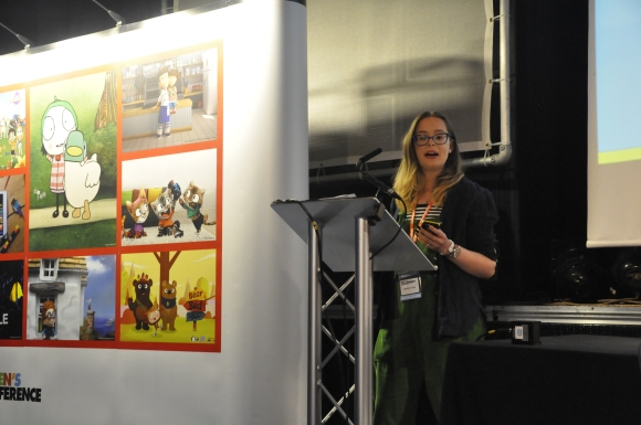 A woman stood at a lectern wearing green dungarees pictured mid-sentence. Next to her is a large board covered in pictures and there's a large screen on the right of the picture with a powerpoint presentation