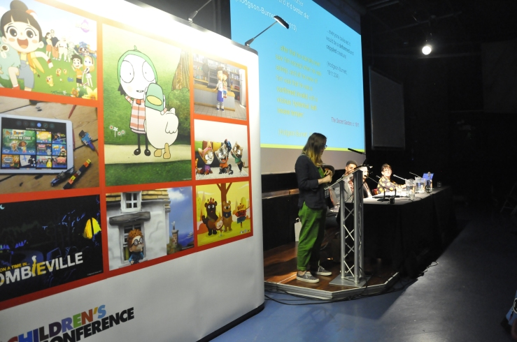 A woman stood at a lectern wearing green dungarees. You cannot see the front of her face. Next to her is a large board covered in pictures and there's a large screen on the right of the picture with a powerpoint presentation.
